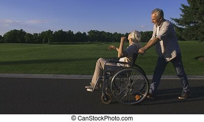 Man with wife in wheelchair enjoying outdoors