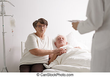 Man with wife listening diagnosis