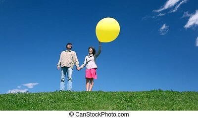 Man with woman holding hands with bubble stand on hill