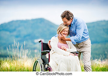 Man with woman in wheelchair - Senior man with woman in...
