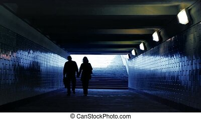 man with woman walking in underground passage to camera, joined hands