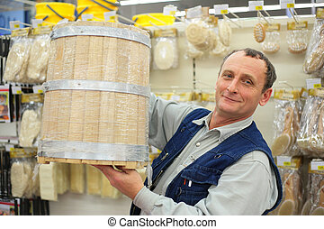 Man with wooden barrel in store