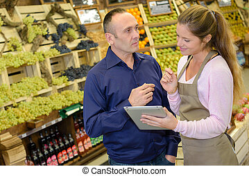 Man with worker holding tablet in vegetable store