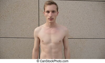 Man without a shirt posing for camera