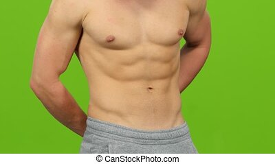 Man without shirt measures volume of his waist. Green screen...