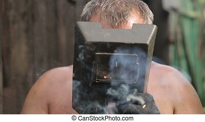 Man Without Shirt Welding - rural man is welding in the...