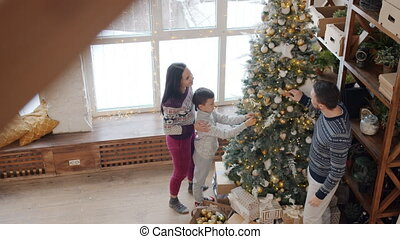 Man, woman and boy putting beautiful decorations on Christmas tree at home