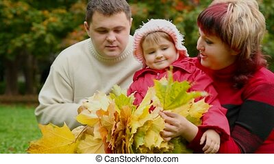 man, woman and little girl collect leafs In autumn park
