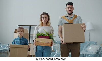 Man woman and little girl happy family are holding boxes smiling looking at camera during relocation to new apartment. People and house concept.