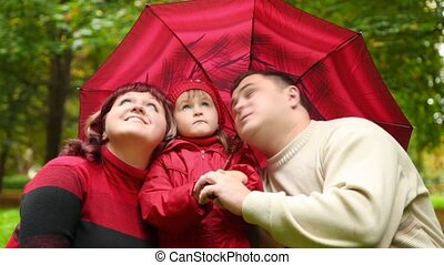 man, woman and little girl sitting under umbrella and looks at sky