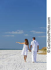 Man Woman Couple Walking Pointing on Empty Beach