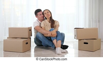 man woman in jeans sit on light floor in new house hugging