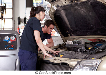 Man Woman Mechanic - A man and woman mechanic working on a...