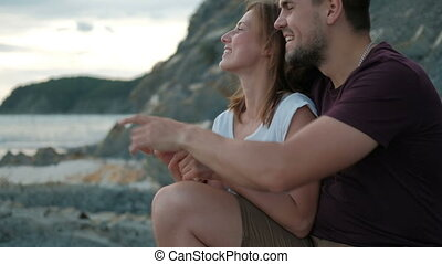 Man woman sitting in hug on shore on stone watching sunset