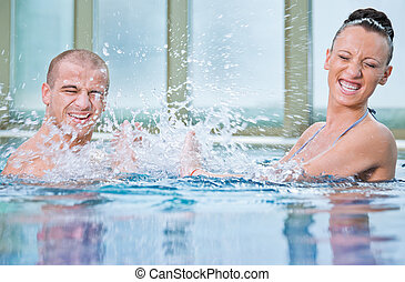 man woman young splashing swimming pool