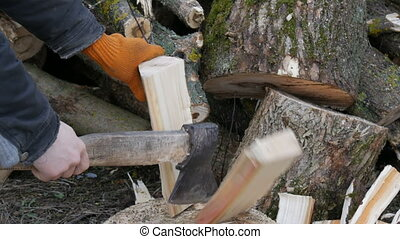 Man woodcutter chops tree trunks with an ax for firewood - A...