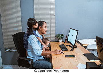 asian businessman working from home while babysitting. parent with child working at home