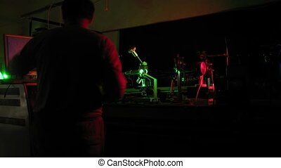 Man work in darkness in laser experimental station, time...