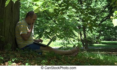 man work with laptop sitting back to tree in nature park. 4K