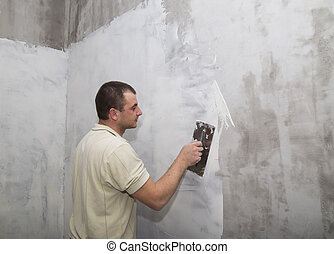 Man worker applying putty