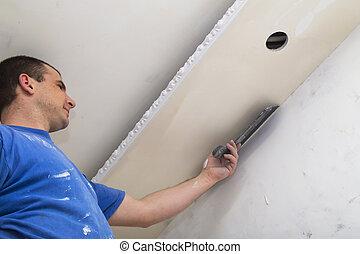 Man worker applying putty