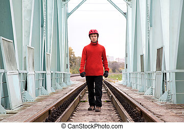 man worker blindly in a helmet stands on the rails bridge