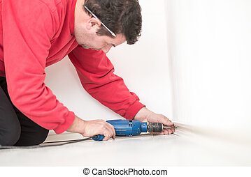 Man worker in red shirt kneeling on the floor drilling a hole