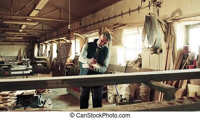 Man worker in the carpentry workshop holding wood.