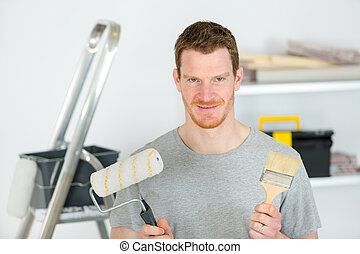 man worker is holding paint brushes