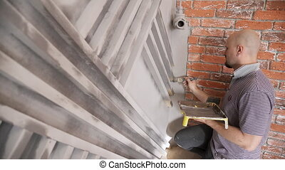 Man worker painting wall boards repair in house
