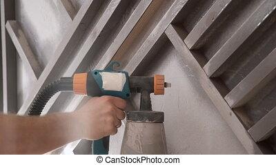 Man worker painting wood boards with spray gun repair in...