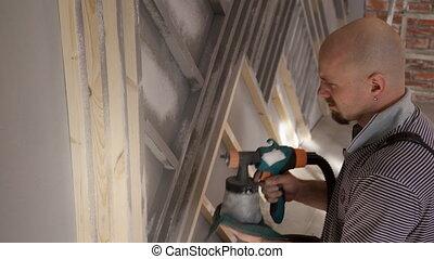 Man worker painting wood with spray gun repair in house