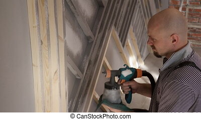 Man worker painting wood with spray gun repair in house
