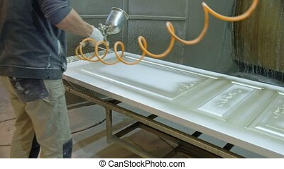 man, worker paints the door. The process of making wooden doors. production of interior doors of wood