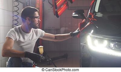 Man worker polishing car on a car wash. - Man worker...