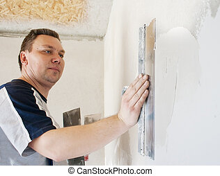 man worker putting plaster on the wall