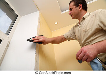 Man Worker putting up wallpaper