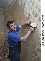 Man worker removing old wallpaper during overhaul