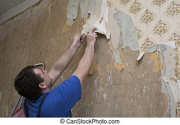 Man worker removing old wallpaper during renovation