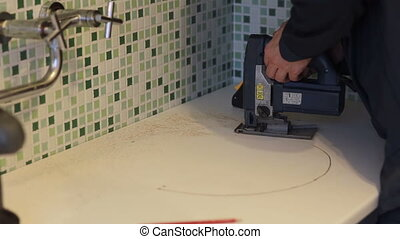 man worker using a fret saw. kitchen assembly. - man worker...
