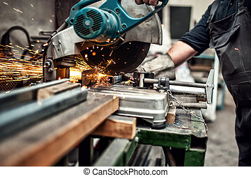 man, worker using a slinding compound mitre saw with ...