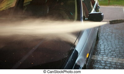 man, worker, washes the car. car wash using high pressure water jet
