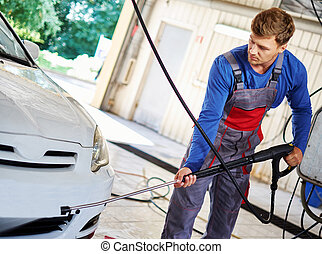 Man worker washing car on a car wash