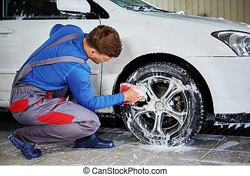 Man worker washing car's alloy rims on a car wash