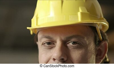 Portrait of happy adult man working as engineer with hardhat. Slow motion