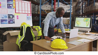 Man working at a desk in a warehouse 4k
