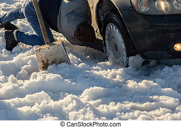 man working at car stuck in snow on knee with shovel at daylight offroad