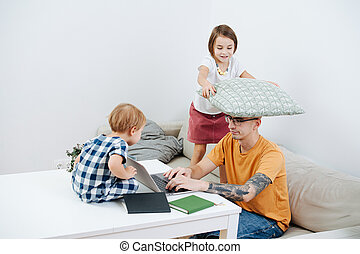Man working at home during isolation, while his kids trying to set him off