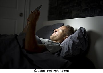 Man working at night, lying on the bed