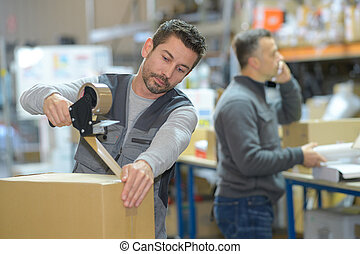 man working at warehouse while manager on the phone